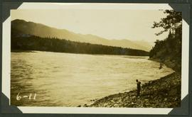 Unidentified man standing on the rocky shoreline of the Peace River (?)