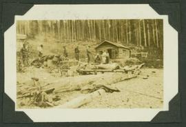 Survey crew and supplies outside the cabin of a man and wife travel writing team