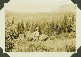 Al Phipps standing beside a horse, tall grass stands before them and a forested landscape and mou...