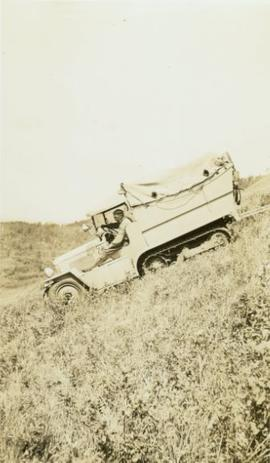 Man driving a Citroen half-track down a grassy slope