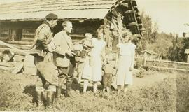 Balourdet and Charles Bedeaux standing with two young women and two children beside Westergaard Ranch on the Halfway River