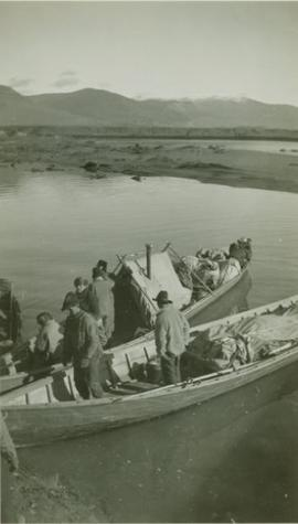 Men standing in supply laden canoes next to Pete's Toy bar on the Peace River
