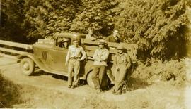 Six unidentified men posing for a photo in or by a truck next to the bridge over Little Qualicum River