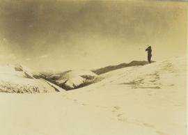 Lone man surveying the landscape from a snowy peak