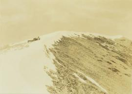 Unidentified man lying down on a snow covered peak looking for game (?)