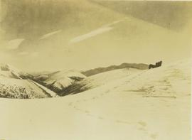 Unidentified guide laying on his back on a snow covered mountain slope searching for game through...