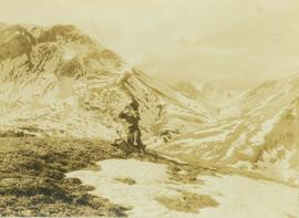 Unidentified guide sitting on top of a mountain peak searching for game through a pair of binoculars