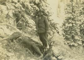 Guide, Bruce Otto, standing next to felled moose