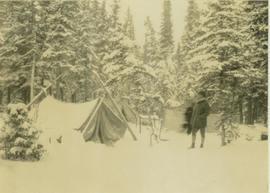Two unidentified men standing at the snow covered campsite