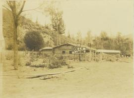 Peace River log cabin featuring two signs