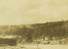 Two unidentified men standing along the rocky shores of the Peace River