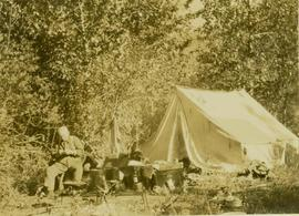 Dan Mosher (?) sitting beside a tent at Camp No.5