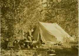 Dan Mosher (?) next to a tent at Camp No.5
