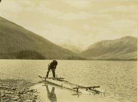 Johnny Napolean using an auger to build a makeshift raft on Muinok Lake