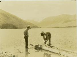 Johnny Napolean  and Pete Callao building a makeshift raft on Muinok Lake