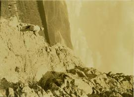 Unidentified man scaling a cliff in search of game