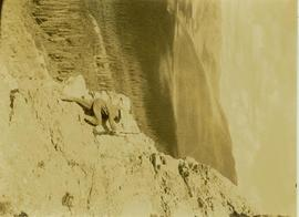 Prentiss Gray, rifle in hand, scaling a cliff in search of game