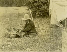 Pete Callao sitting on the ground near a tent fixing a saddle