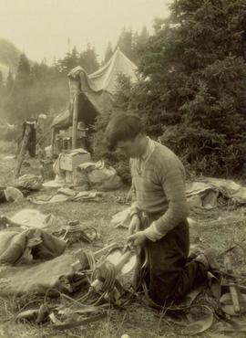 William Taylor repairing a pack saddle at camp
