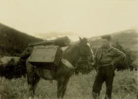 Pete Callao standing next to the pack horse loaded up with Gray's camera equipment