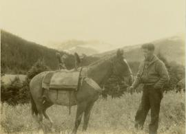 Pete Callao standing next to the pack horse wearing a saddle designed to carry Gray's camera equipment