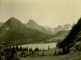 Forested valley with lake rising to snow capped mountain peaks