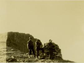 (L-R) Bob Potts, Joe (?) Callao and an unidentified man looking for game from a hilltop cairn