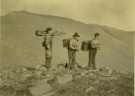 (L-R) Billy Taylor, Johnny Napolean and Pete Callao stand on a rocky mountain top carrying camera...