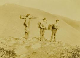 (L-R) Billy Taylor, Johnny Napolean and Pete Callao standing on a rocky mountain peak carrying camera equipment