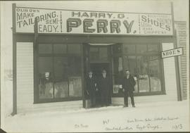 Mr. Moore, HGT Perry & Parr Brown standing in front of Harry G. Perry's Tailor Shop, For...