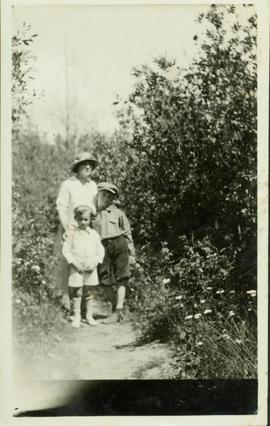 Woman standing on a dirt path with two young boys
