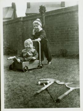 Family photographs from England: John pushing Christine in a wagon