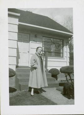 Woman (Florence Hawkes ?) standing outside of a house
