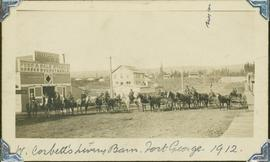 Group of horse drawn carriages gathered next to W. Corbett's Livery Barn in Fort George