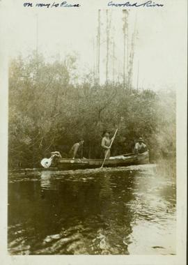 Three men in a boat being poled up the Crooked River