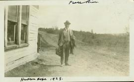 HGT Perry standing with coat and briefcase in hand on a dirt road in Hudson Hope, BC