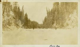 Two unidentified men standing on a frozen river