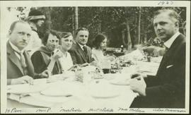 Harry Perry sits with Mrs. Perry, Mrs. Parker, T.D. Pattullo, Mrs. McLean and Alex Manson at a picnic table at a Liberal Party picnic