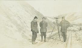 Three men stand with a leveling instrument in the middle of a set of railway tracks in the winter