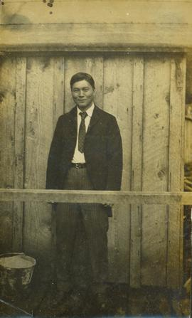 Man of Japanese descent wearing suit and tie and posing for a photograph