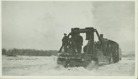 Two unidentified men standing on a railroad snow plow connected to the front of a train which is ...