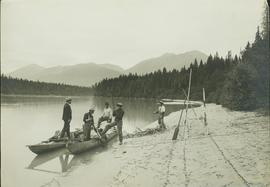 Five unidentified First nation men standing in, or next to, a boat pulled up to a sandy bank alon...