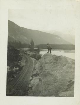 Man (R.A. Harlow?) standing on a large boulder overlooking a railway track