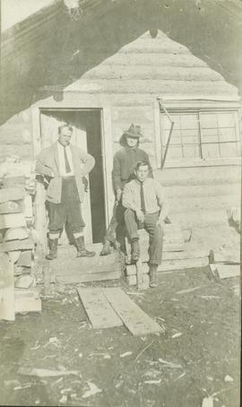 Three men posing outside of a log building