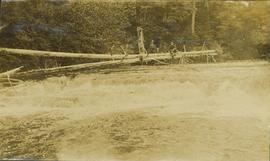 Unidentified man sitting on a felled tree which spans over a small waterfall