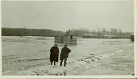 Two unidentified men standing on a snowy 'berm' in the flooded CNR yard at Prince George