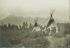 Unidentified First Nations family standing in front of the tee pee structures at Tete Jaune Cache...