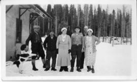 A group of 5 males, two females and a dog posing for a photograph at Lindup railroad station near