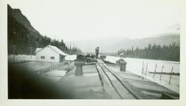 Two unidentified men surveying the flood waters at or near the Pacific Station on the Skeena River