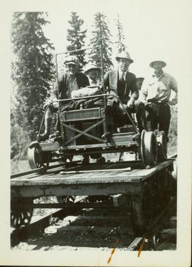 Small flatcar loaded with four men and a speeder